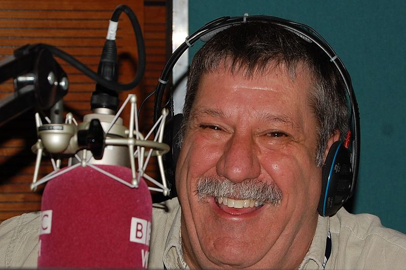 Smiling man, wearing headphones, at microphone